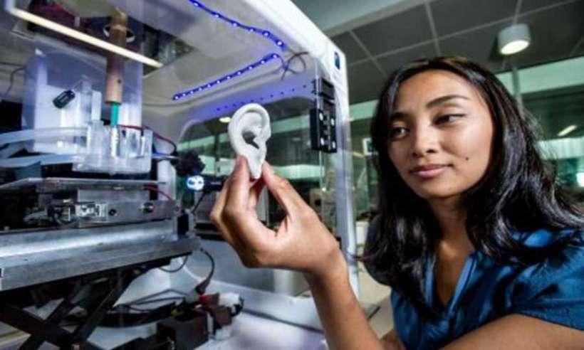 Kobieta trzyma w dłoni wydrukowane na drukarce 3D ucho z tworzywa sztucznego