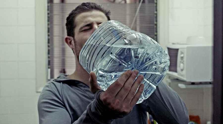 Mężczyzna pijący wodę z butelki